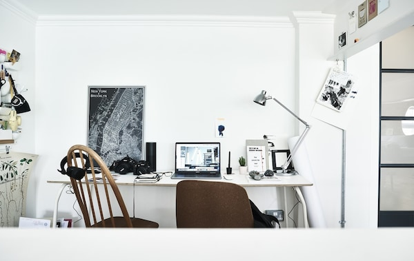 A home workspace with two chairs and white desk.
