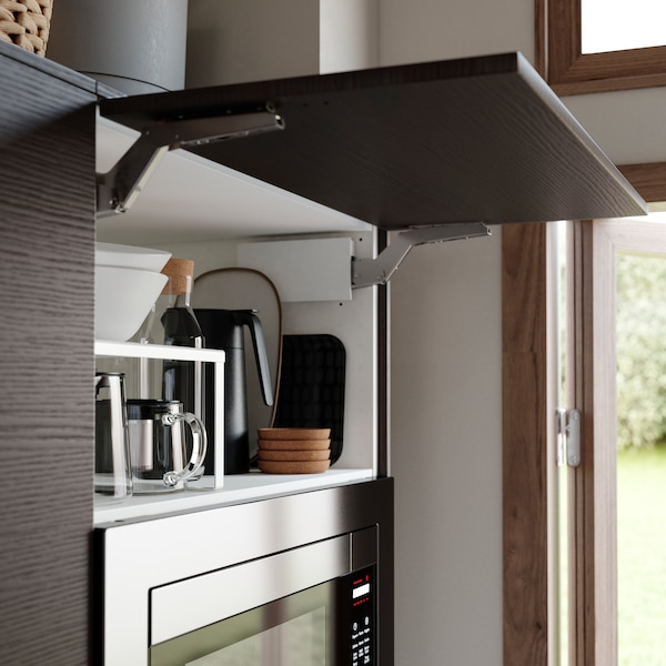 A horizontal kitchen door in dark brown ash effect is open. A black thermos, bowls and a glass carafe are stored inside.