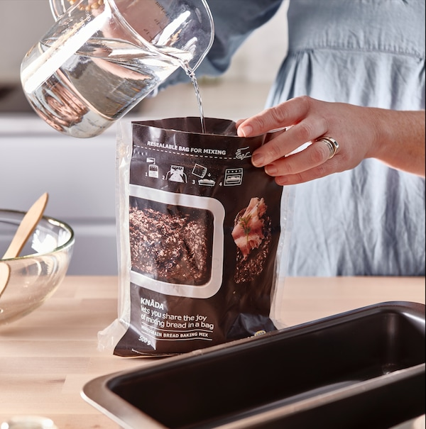 A jug pours water into a container to prepare the mixture of homemade bread dough