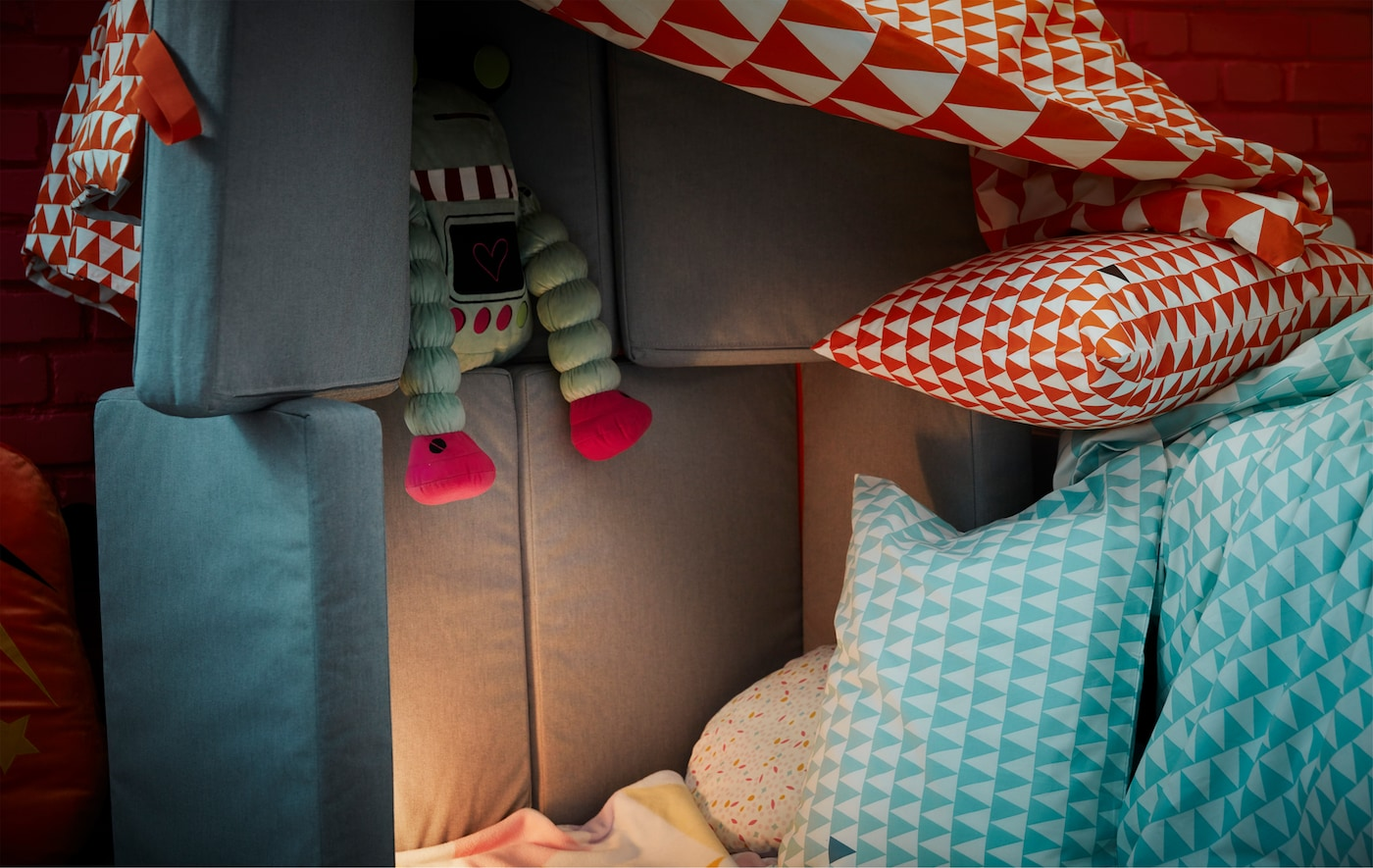 A jumble of bedsheets, cushions, soft toys and a foldable mattress created as a children's fort.
