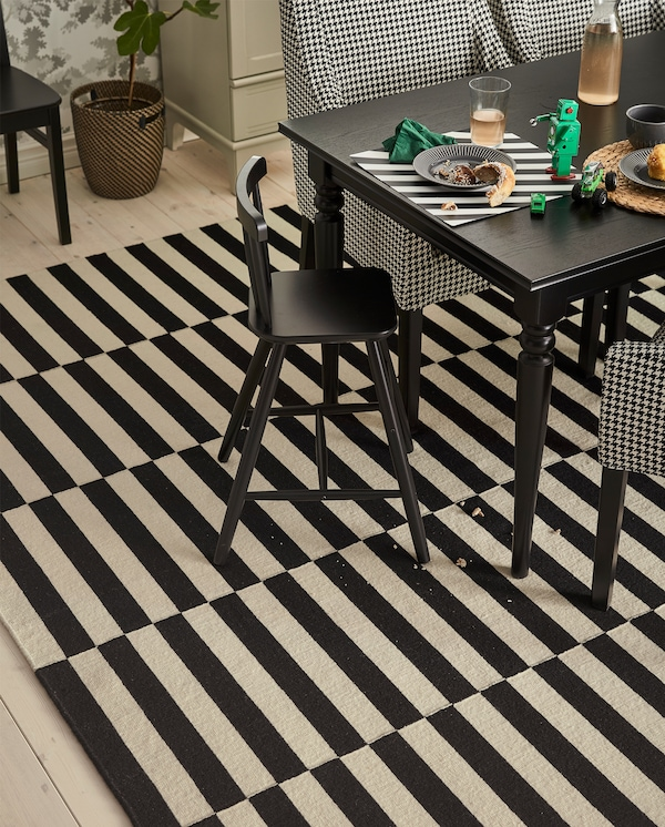 A junior chair stands at a table. Below lies a black/white striped STOCKHOLM low pile rug with some crumbs from a cake.