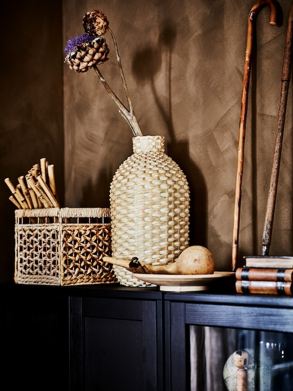 A KAFFEBÖNA bamboo vase holding a dried artichoke flower amid other artful objects atop a pair of dark HAVSTA cabinets.