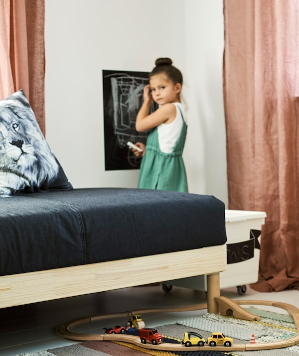 A kid draws on a chalkboard wall sticker in a room with a toy box, pink drapes, grey sofa and LILLABO train set with toy cars on a stripy rug.