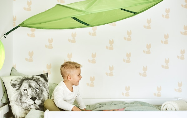A kid sits on a bed with green duvet and a cushion printed with a lion's face, above the bed is a green leaf-shaped canopy.