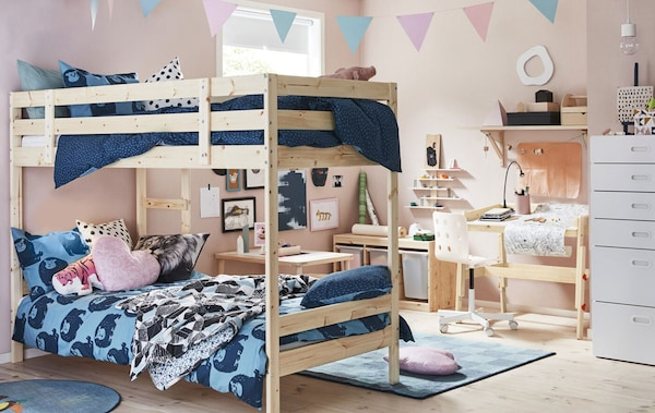 A kid's bedroom with pink walls, bunk bed with blue bedding, and light wood desk and storage.