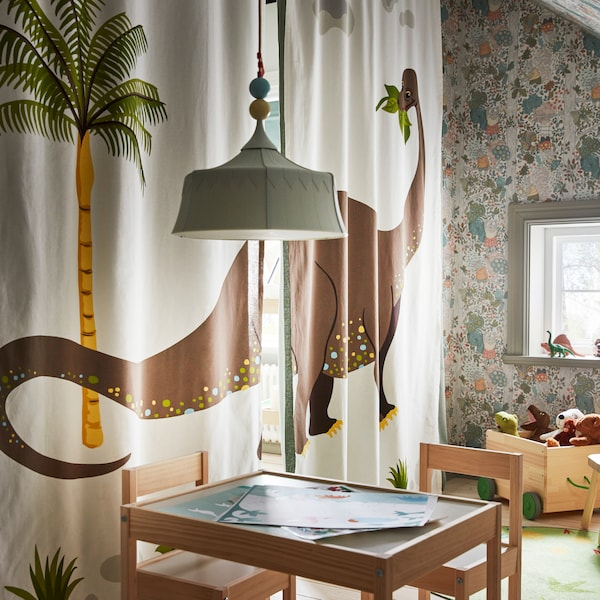 A kid's room with a table and chairs, and scattered toys. The fourth wall is formed by dinosaur-motif curtains drawn shut.