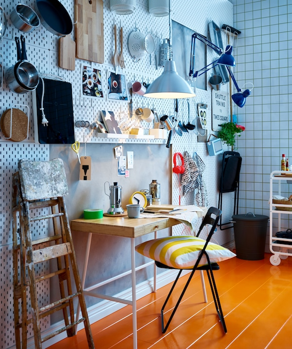 A kitchen area with perforated wall tiles and kitchen utensils hanging from hooks, with a breakfast table and folding chairs.