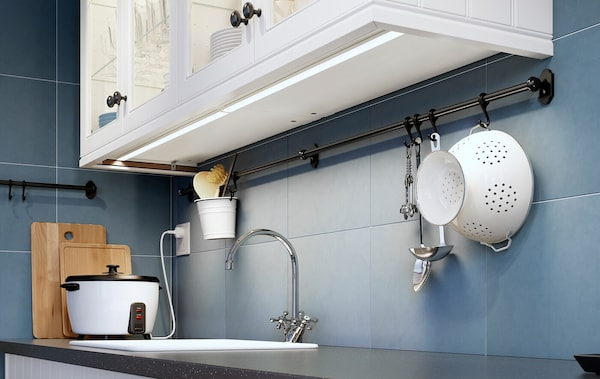 A kitchen cabinet with strip lighting attached to the underside.