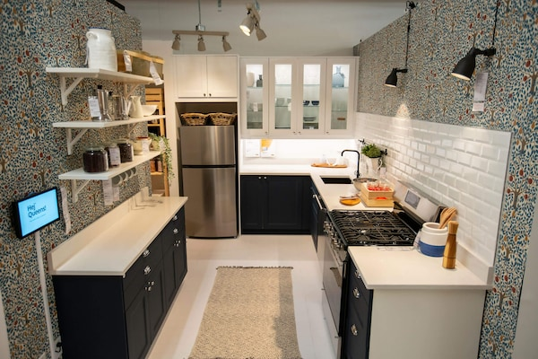 A kitchen display featuring a dark kitchen cabinet front with white countertops and lighting above.