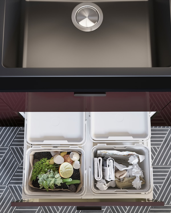 A kitchen drawer is open and inside is a light grey HÅLLBAR waste sorting solution with food waste and paper recycling.