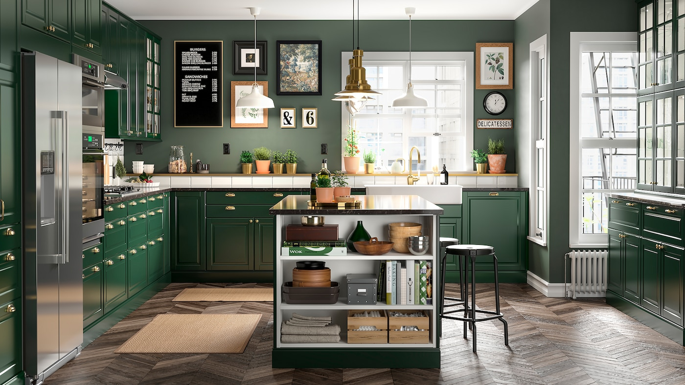 A kitchen in dark green with a kitchen island, black bar stools, a brass-colored faucet and two jute rugs.