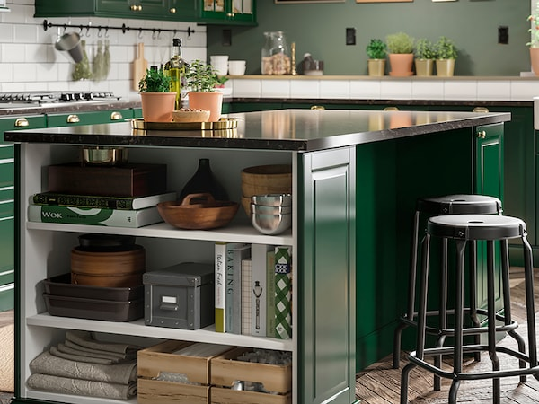 A kitchen in dark green with a kitchen island, black bar stools, glass doors and pendant lamps in brass colour and white.