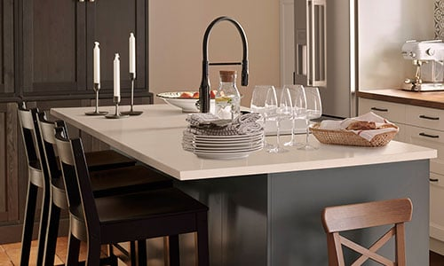 A kitchen in dark grey featuring a kitchen island with quartz countertop and black bar stools.