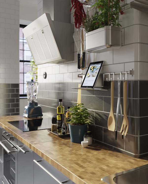 A kitchen in stainless steel, a wood worktop, fresh herbs and a wall-mounted rail with a tablet on a tablet stand.