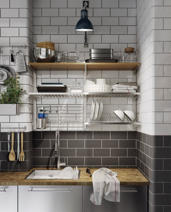 A kitchen in stainless steel with a wood worktop, a blue work lamp and a dish drainer, rails and shelves are wall-mounted.