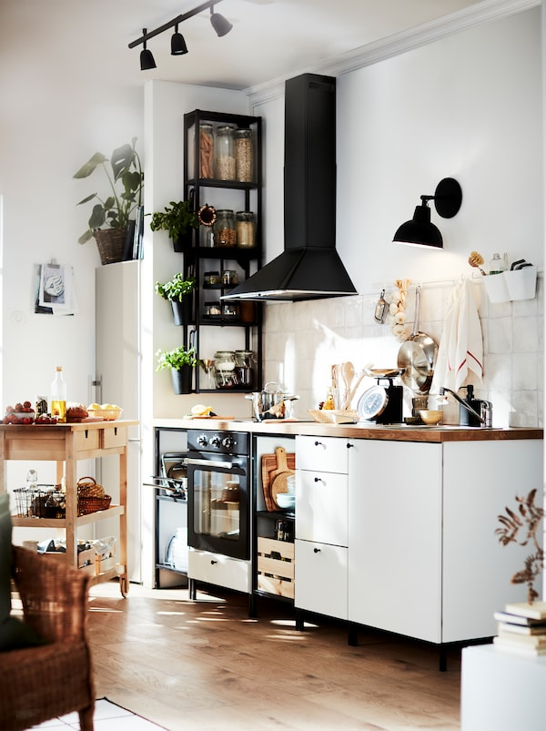 A kitchen in white and black with warm wood tones from the floor, the worktop, and a FÖRHÖJA wooden kitchen trolley.