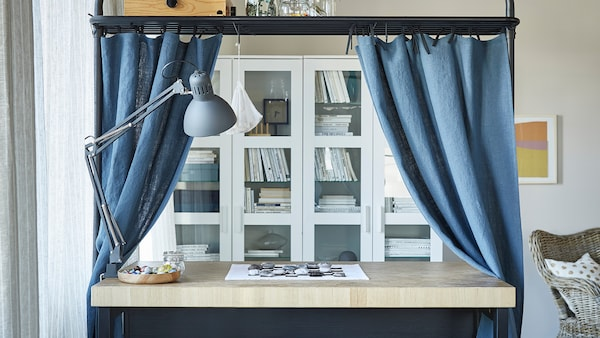 A kitchen island in a living room with the overhead frame used as storage space and a rod for blue curtains.