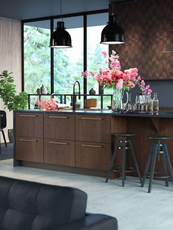 A kitchen island in dark wood, two black bar stools, two black pendant lamps, a vase with pink and red flowers.