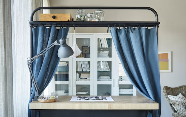 A kitchen island placed in a living room. The overhead frame serving as storage space and decorated with blue curtains.