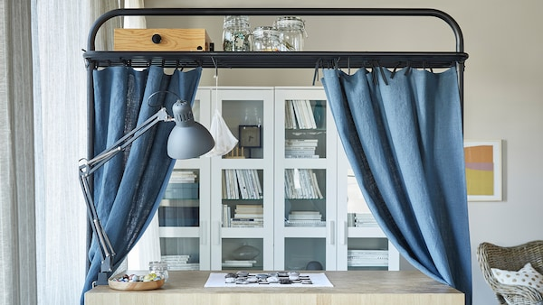 A kitchen island used as a desk in front of white glass cabinets. Curtains hang from the frame.