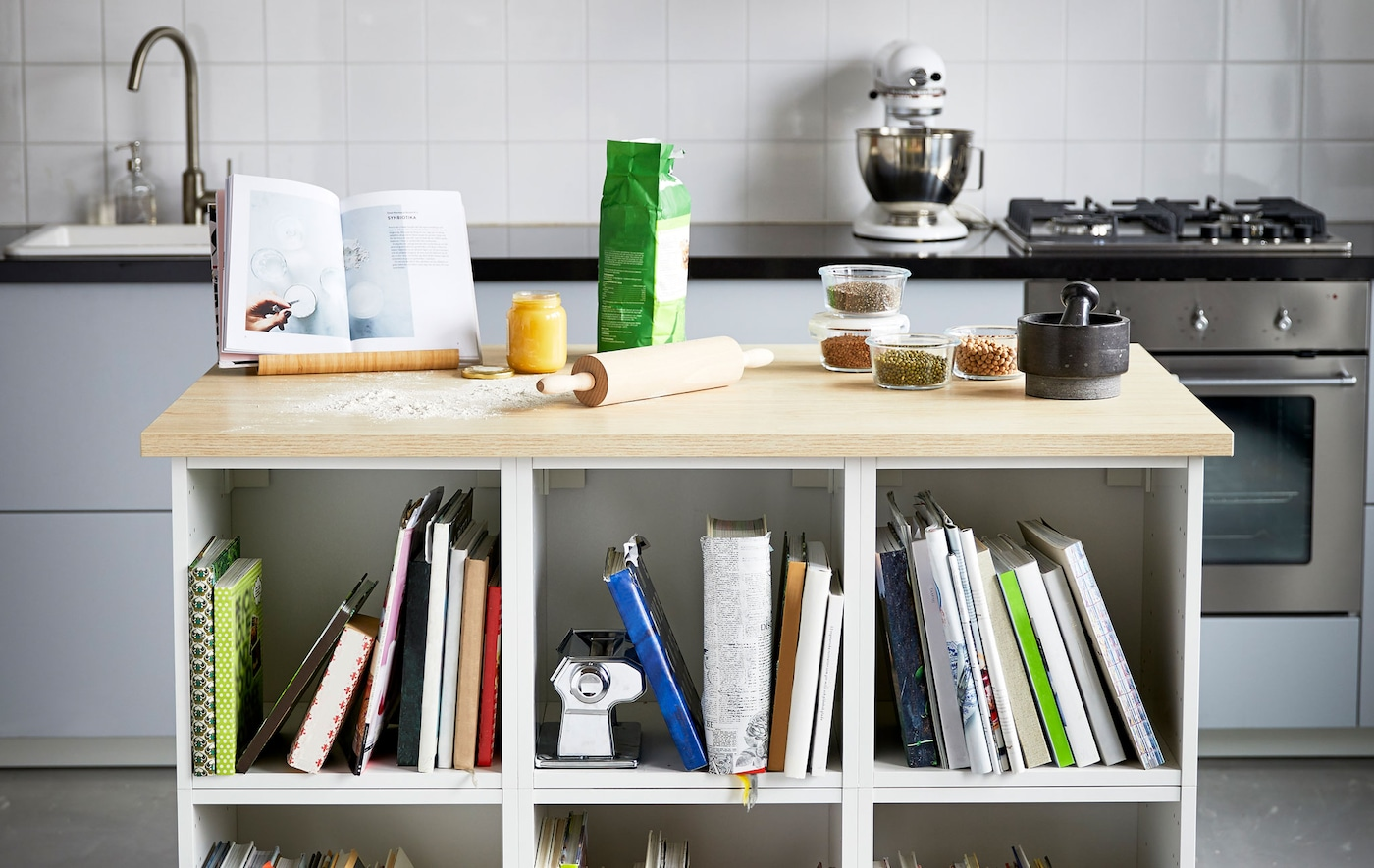 A kitchen island with a wooden countertop and built-in shelves. It's perfect for baking and storing cookbooks.