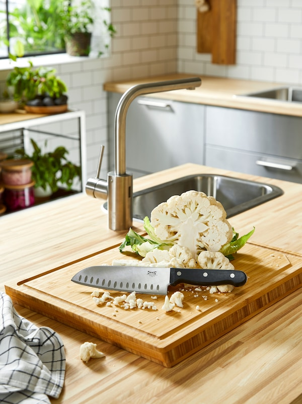 A kitchen island with a wooden worktop and an APTITLIG butcher's block with a kitchen knife and a cut cauliflower.