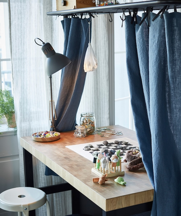 A kitchen island with blue curtains, a play board and jars placed on the work surface.