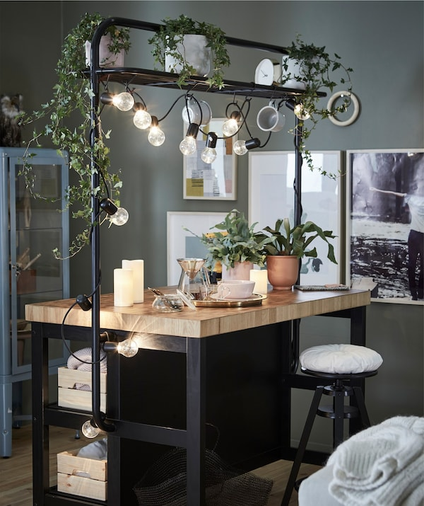 A kitchen island with mood lighting and hanging greenery.