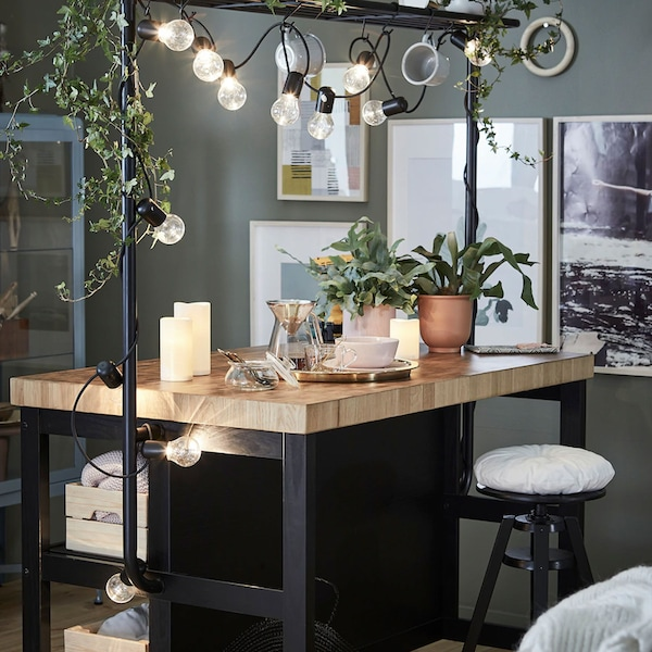 A kitchen island with rack decorated with a black lighting chain and trailing leafy green plants in white plant pots.
