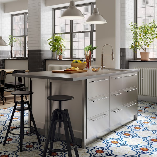 A kitchen island with worktop in concrete effect/quartz and drawers in stainless steel. Two black bar stools stand beside.