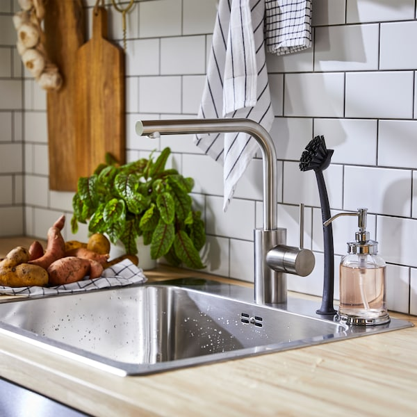 A kitchen mixer tap in stainless steel colour, a sink in stainless steel, a dish-washing brush and black/white tea towels.