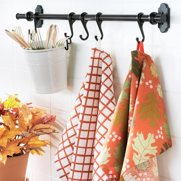 A kitchen rack with utensils and orange tea towels hanging from it.