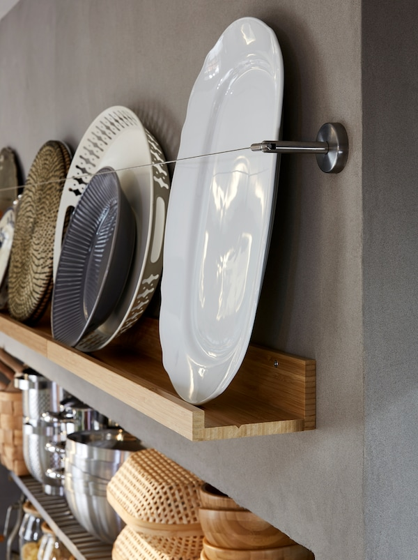 A kitchen storage wall with a wooden MÅLERÅS picture ledge displaying stoneware plates, trays and other kitchen items.