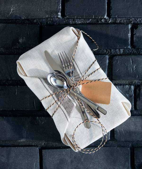A kitchen themed gift wrapped in an IKEA VARDAGEN tea towel.