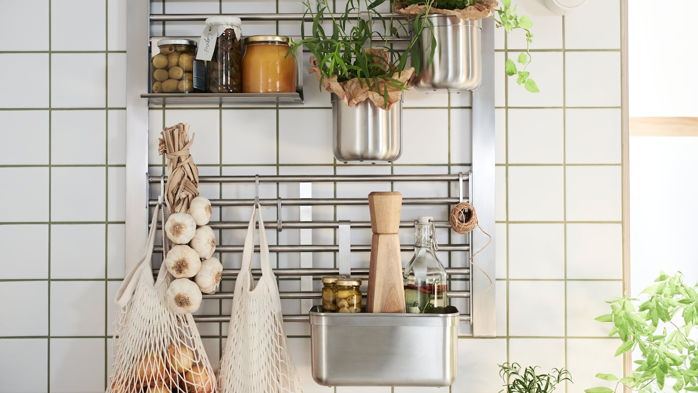 A kitchen wall with a KUNGSFORS wall grid with shelf, hooks and containers, all in stainless steel, holding jars and herbs.