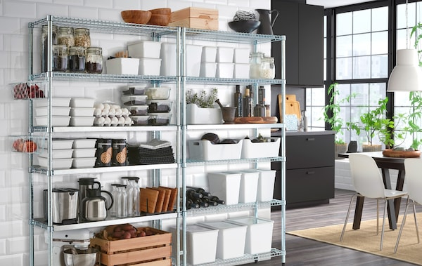 A kitchen wall with freestanding shelving units containing storage organisers and kitchen accessories.