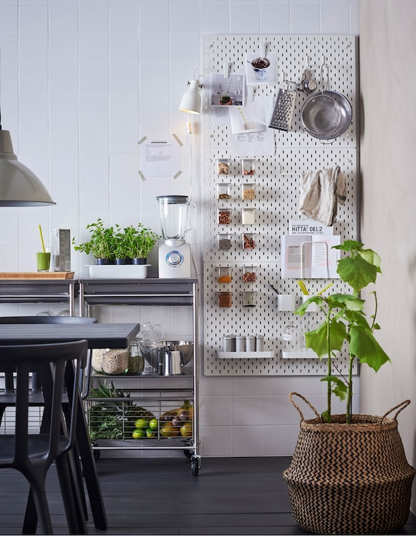A kitchen wall with pergboard holding spice jars and kitchen utensils.