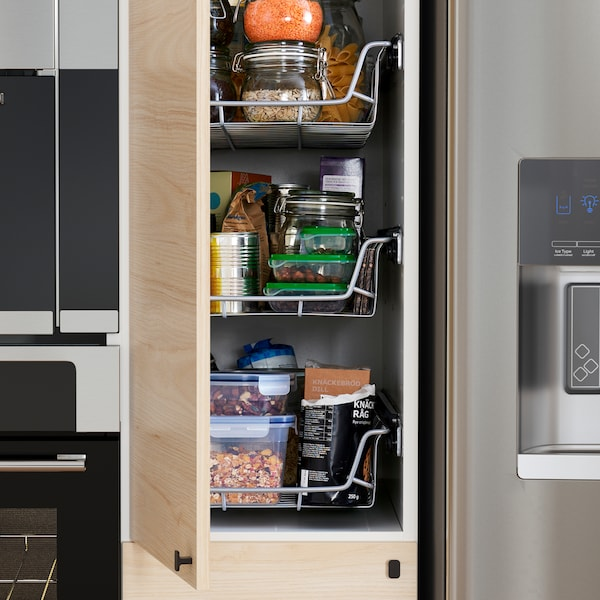 A kitchen with a high cabinet in a light ash effect door that is open to show wire baskets, food containers and more inside.