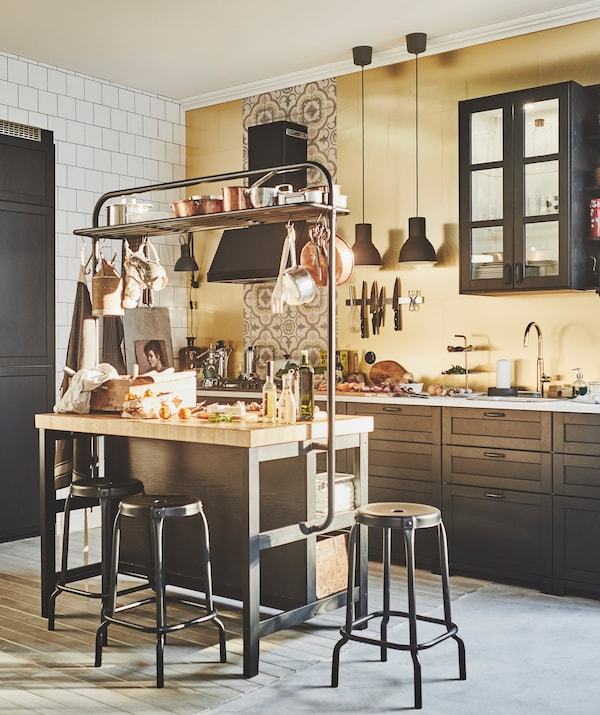 A kitchen, with a kitchen island surround with stools and brass coloured IKEA LYSEKIL wall panels.