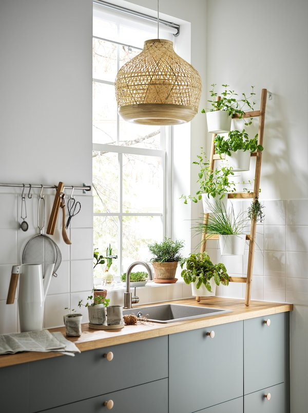 A kitchen with a ladder-like SATSUMAS bamboo plant stand with five plant pots standing on the worktop in front of a window.