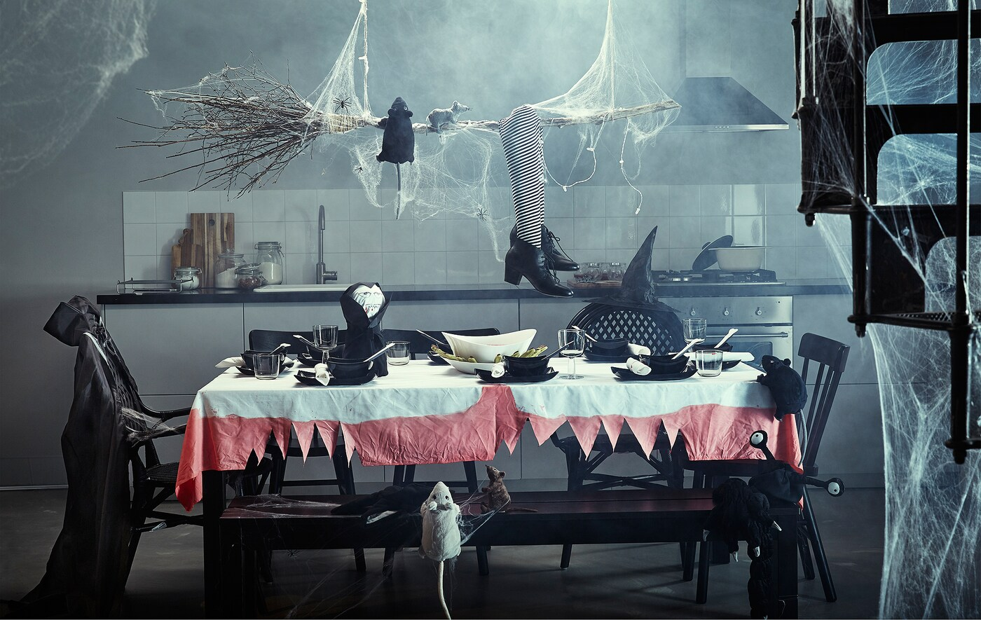 A kitchen with a large table that is full of Halloween decorations.