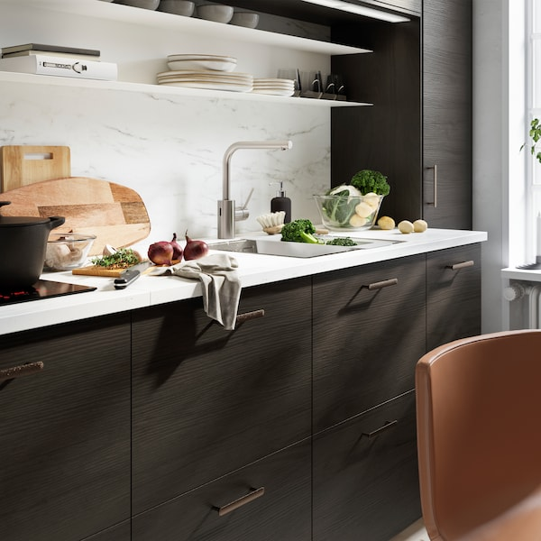 A kitchen with a wall panel and worktop in white marble effect, kitchen fronts in dark brown ash effect and black handles.