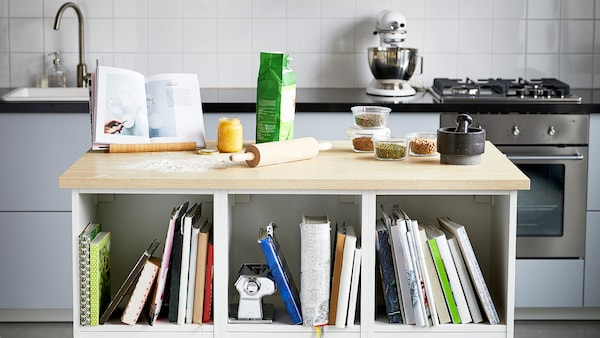 A kitchen with a white island with a wooden countertop with baking tools, glass containers and a black pestle and mortar.