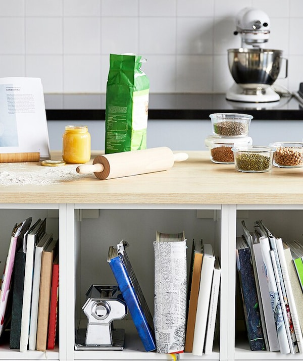 A kitchen with a white island with a wooden worktop with baking tools, glass containers and a black pestle and mortar.