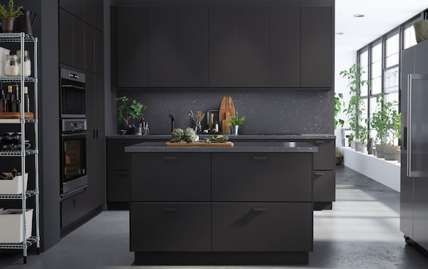 A kitchen with anthracite units, and dark grey walls and dining island.