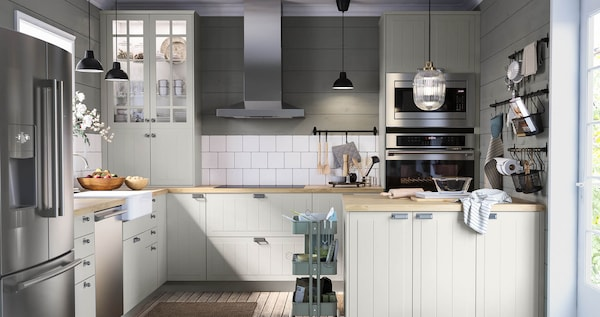 A kitchen with beige door fronts, wood countertops and stainless appliances with white tile against the wall.