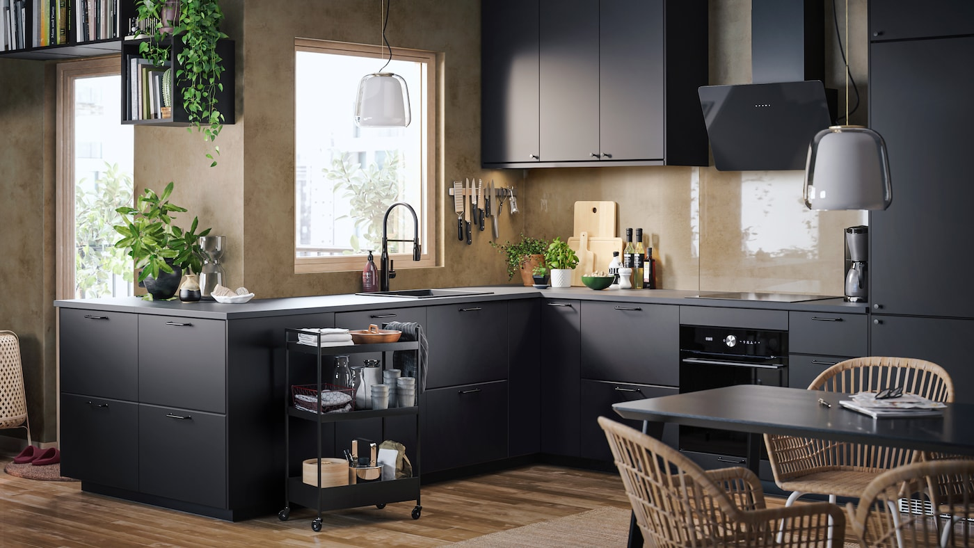 A kitchen with beige walls, wooden floors, KUNGSBACKA kitchen fronts in anthracite and a trolley with kitchen accessories.