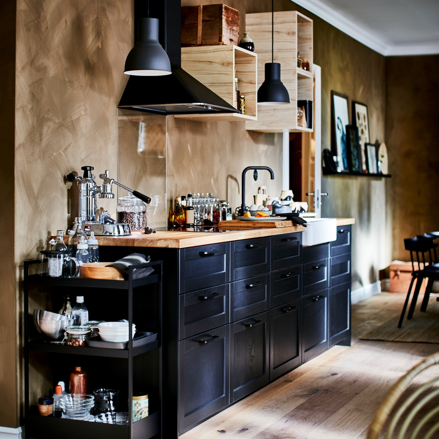 A kitchen with black drawer fronts, a wooden worktop, a black trolley, open wall cabinets and two dark grey pendant lamps.