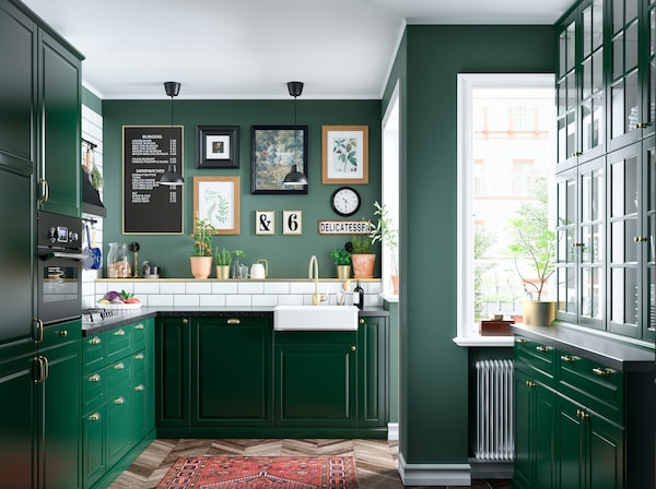 A kitchen with colour coordinated storage, lots of worktops, a cooker and sink and some frames pictures on the wall.