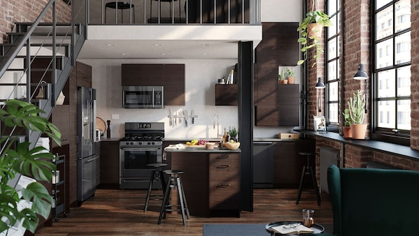 A kitchen with dark brown cabinets and stainless steel appliances.